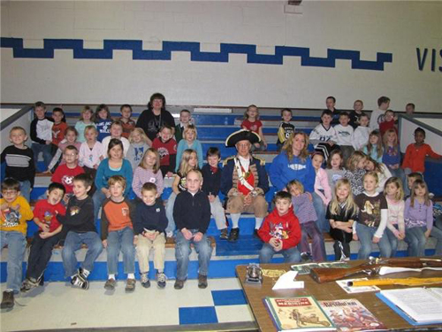 Pictured here is Harry S. Truman Chapter Color Guard Commander, Major General Robert L. Grover on January 23, 2009 presenting an American Revolution Program to First graders at Lone Jack Elementary School in Lone Jack, Missouri.  The presentation included the display and discussion of paper money, coins, Liberty Bell, Sword, Musket, whistle, showing a picture of the Harry S. Truman Chapter 15 Colonial Flags, food rations, uniforms, and a cat of nine lives.