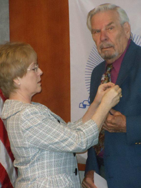 Diana Ritter, Regent, Independence Pioneers DAR Chapter, also participated in the ceremony by placing the SAR Rosette on Compatriot Quint's lapel.