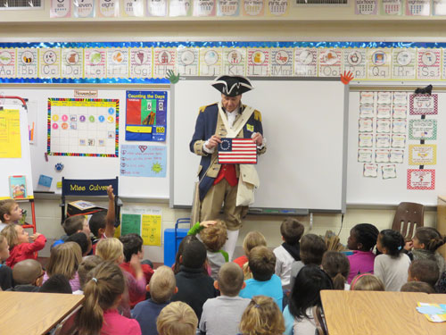 Pictured here is Compatriot Roy Hutchinson, a member of the Harry S. Truman Chapter Color Guard, during a school presentation with first graders at Line Creek Elementary in Park Hill School District on Veterans Day 2014.