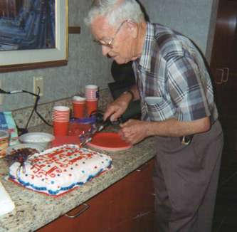 Compatriot David McCann is shown here making preparations to serve the cake.