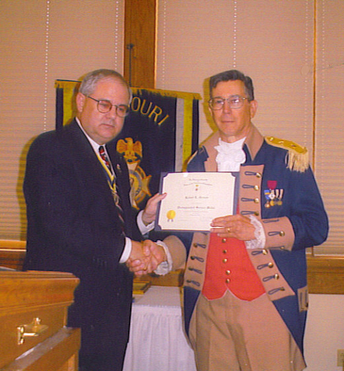 President David N. Appleby presents the Distinguished Service medal and certificate to Robert L. Grover, MOSSAR Color Guard Commander, for his tireless efforts in support of the Color Guard at the 112th MOSSAR Annual State Meeting in Columbia, MO on April 29, 2002