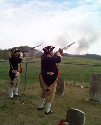 Shown here is  Compatriot Alvin Paris (decendant of Revolution War Patriot James Paris); and Compatriot James L. Scott, Western Color Guard Commander firing their muskets during the Grave Marker Dedication Ceremony for American Revolution War Patriot James Paris on Saturday, March 24, 2012.